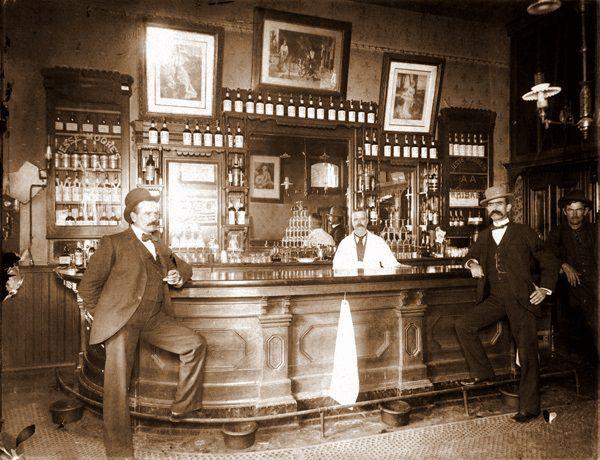 Seepiansävyisessä kuvassa on vanha amerikkalainen baari, jossa tiskin edessä seisoo viiksekkäitä knallipäiviä miehiä poseeraamassa.