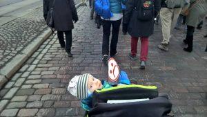 Kuvassa lapsi rattaissa kädessään kyltti, jossa surunaamahymiö.
