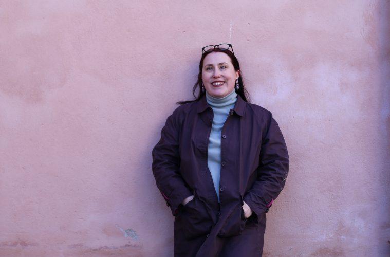 Minna Sumelius nojaa vaaleanpunertavaa seinää vasten ja katsoo hymyillen suoraan kameraan.