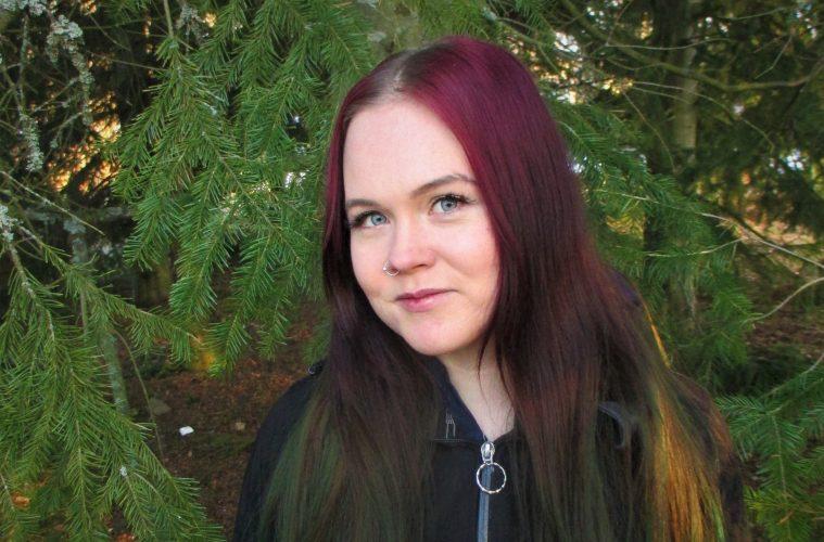 Noora Kyllönen hymyilee ja katsoo kameraan hieman sivuittain. Taustalla on vihreä havupuu.