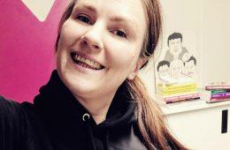 Kuvassa Milla Pyykkönen katsoo hymyillen kameraan. Yllään hänellä on musta huppari ja taustalla toimistotila.