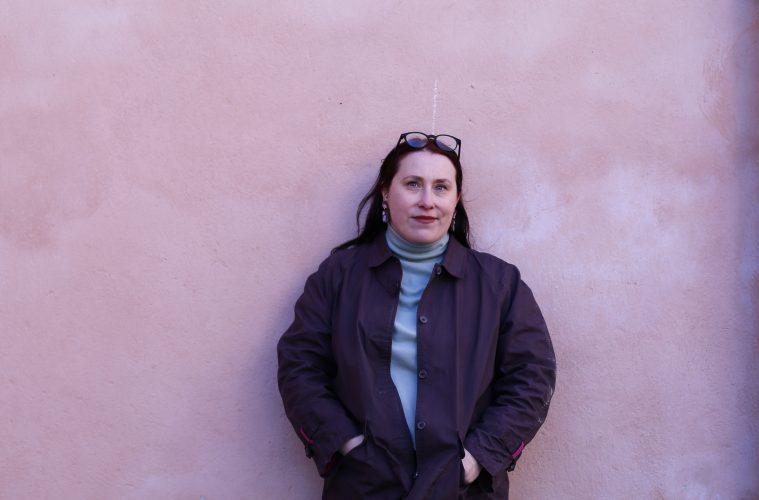 Minna Sumelius katsoo suoraan kameraan kädet taskuissa, taustalla vaalean lila/punertava seinä.