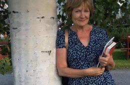 Ulla-Leena Alppi katsoo hymyillen kameraan, nojaa koivunrunkoon ja pitelee kädessään pientä kirjapinoa.