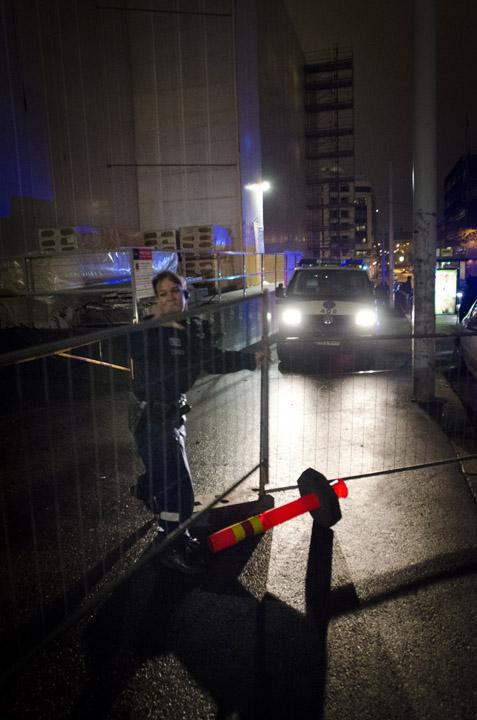 Poliisi purkaa mielenosoittajien poliisiautolle työmaa-aidoista rakentamaa ansaa.