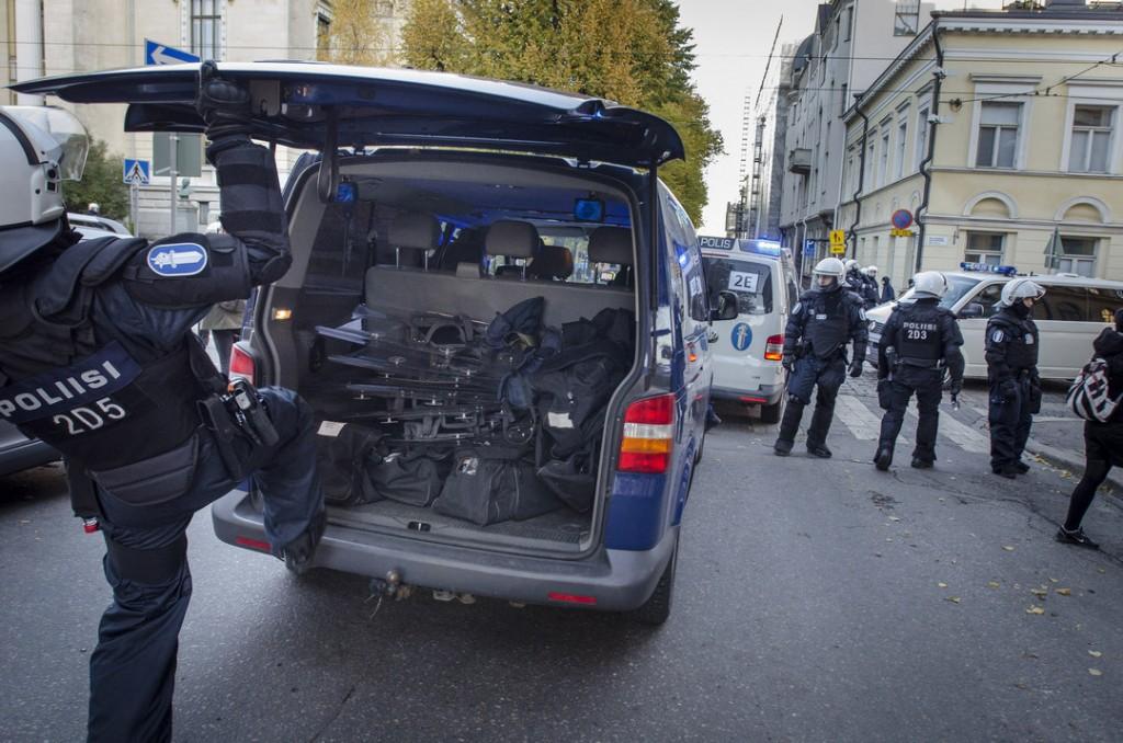 Kirkkokadun ja Snellmaninkadun risteyksessä poliisi potki kilpiä takaluukkuun.