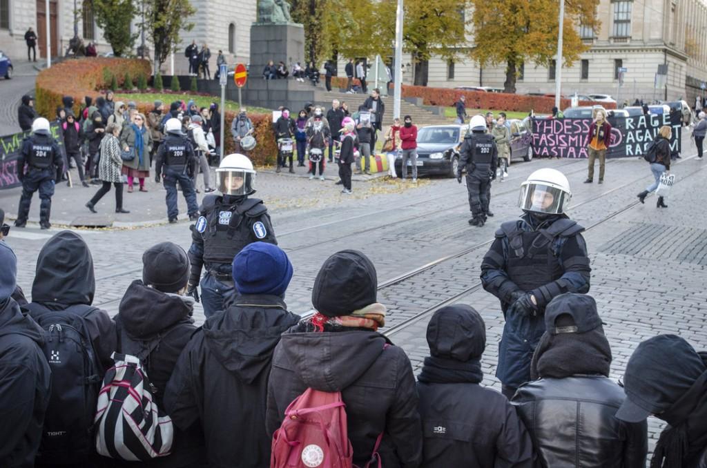 Poliisi vartioi katua tukkivia ihmisiä edessä ja takana.