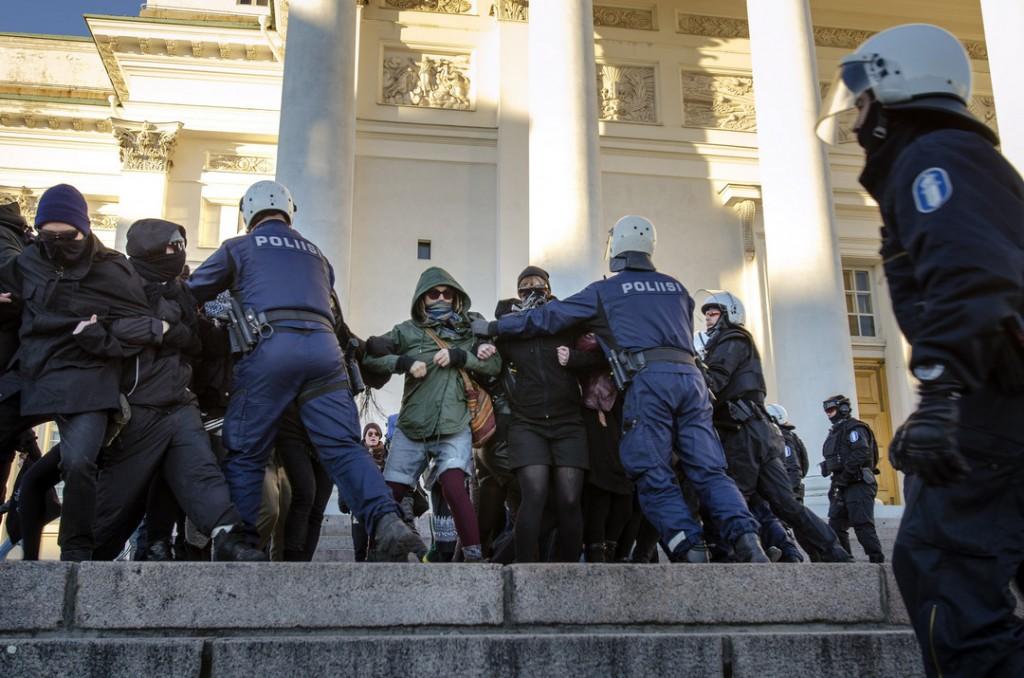 Poliisi kiipesi portaat ylös ja alkoi voimakkaasti työntää ja repiä rasisminvastaisia mielenosoittajia taaksepäin.