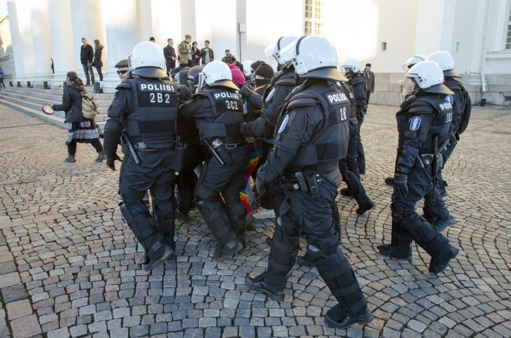 Mellakkapoliisit kuljettivat viimeisiä mielenosoittajia kovakouraisesti pois.