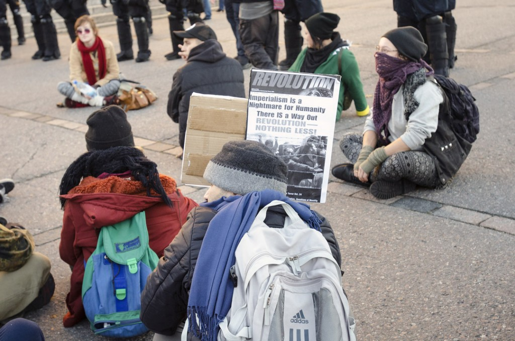 Mielenosoittajat istuivat ja solvasivat poliisia.
